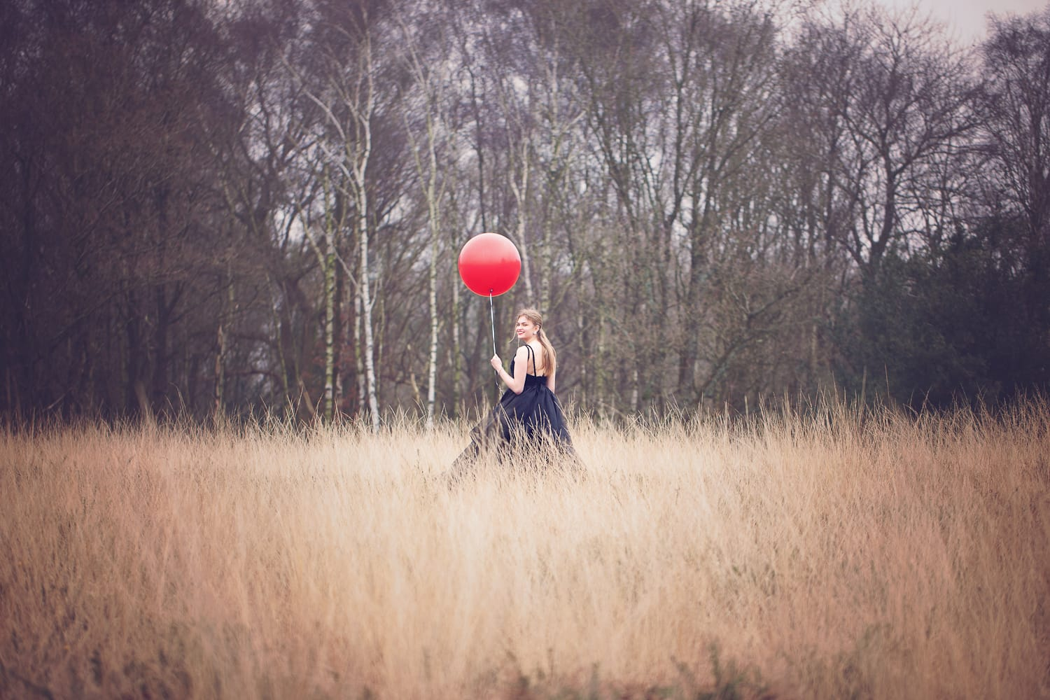Girl with red balloon on Forest