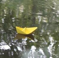 Gevouwen bootje van geel papier dat voortdrijft op rustig water