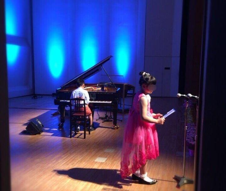 舞台でピアノを弾く男の子とマイクで喋っている女の子