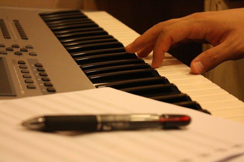 電子ピアノ、五線紙、ペン、大人の手、黄色い照明