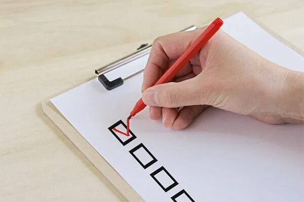 チェックリストとペンを持つ手