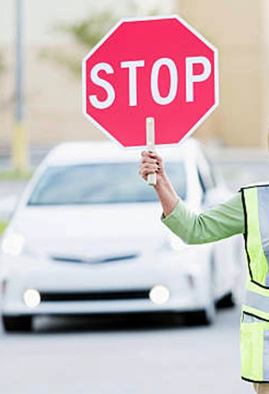 School crossing guard (Hispanic mature woman, 50s) helping children walk across street. Focus on woman.