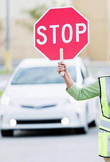School crossing guard (Hispanic mature woman, 50s) helping children walk across street. Focus on woman.