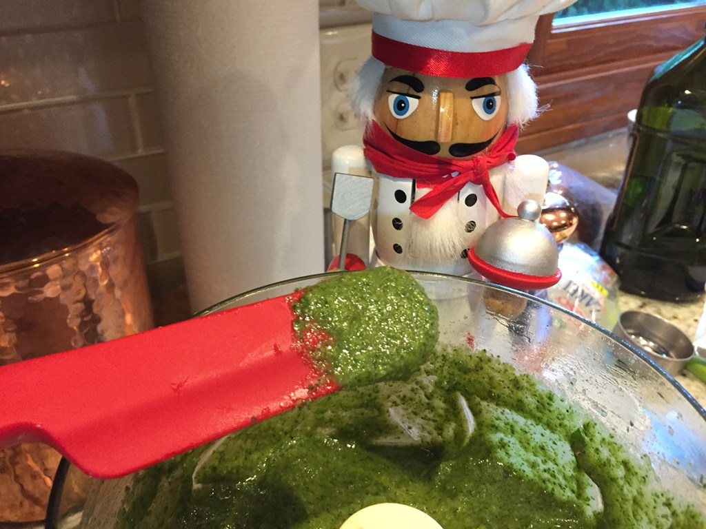 Pureed basil pesto in a food processor with a small amount on a red rubber spatula for tasting. There's a nutcracker in the foreground who looks like a chef.