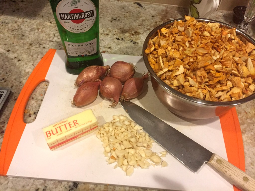 chopped chanterelles, chopped garlic, partial stick of butter, bottle of dry vermouth and a chef kife on a white cutting board