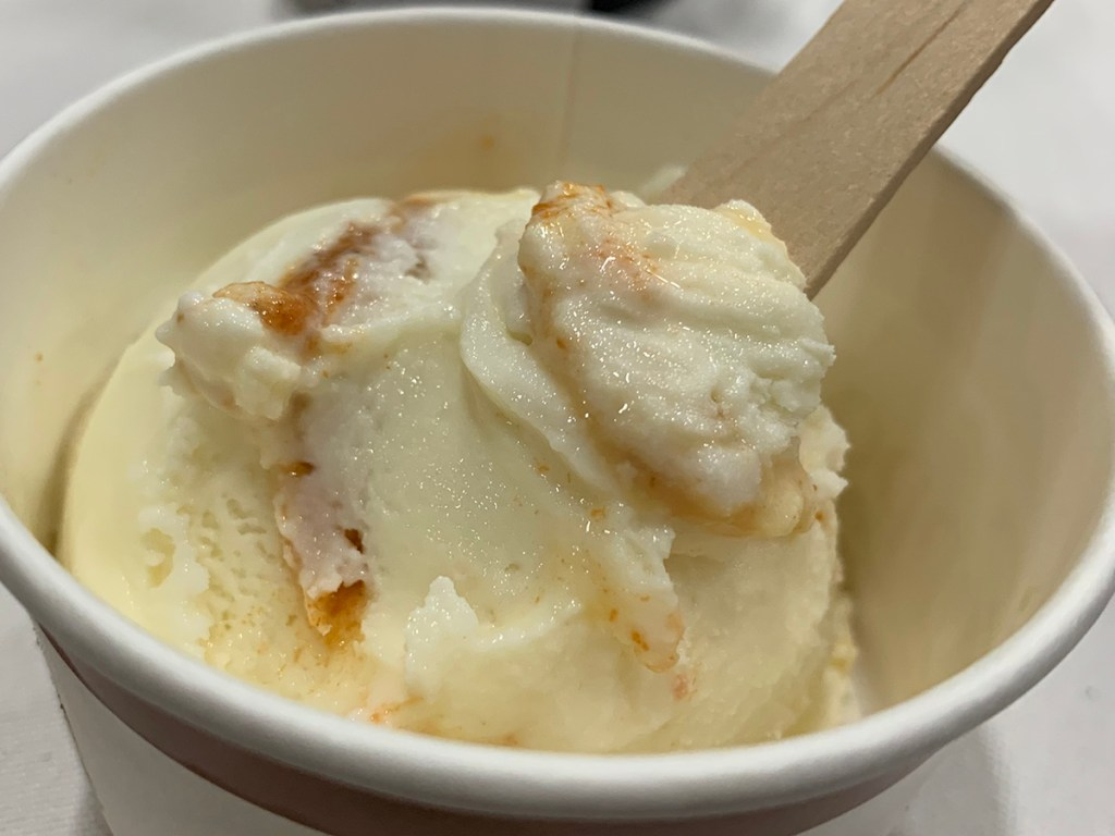 single scoop of white and caramel swirled ice cream in white paper bowl with wooden spoon