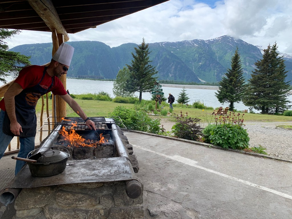 chef cooking on outdoor grill with mountains in the background