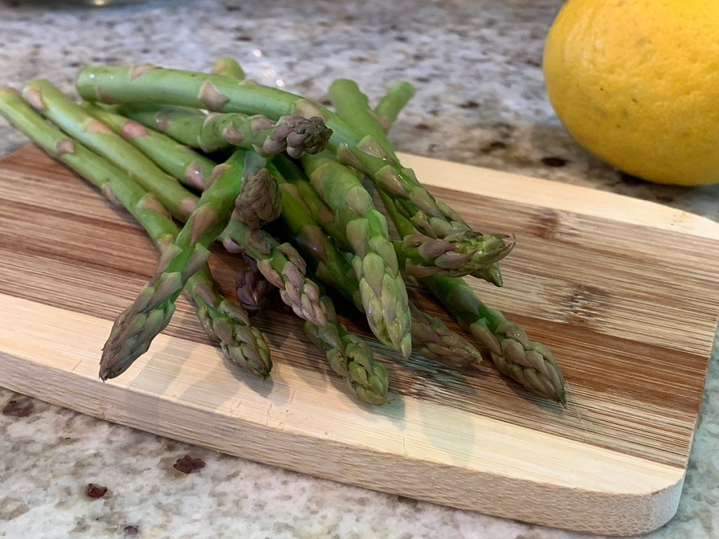 asparagus on a bamboo cutting board, on a granite countertop with partial view of a lemon