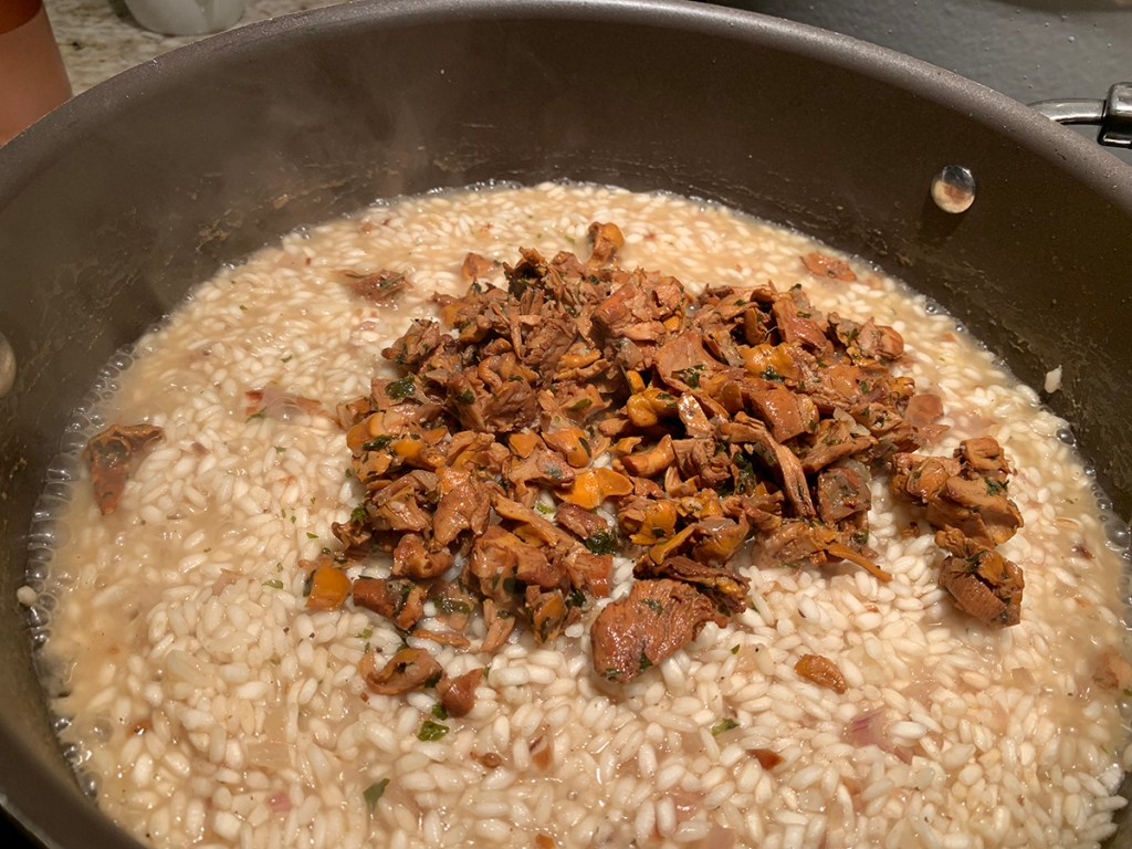 a pile of chanterelle duxelles on top of simmering rice in skillet