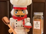 spice blend of oregano, garlic powder, cumin & cayenne pepper in a jar next to a nutcracker that looks like a chef. He's holding a copper measuring spoon.