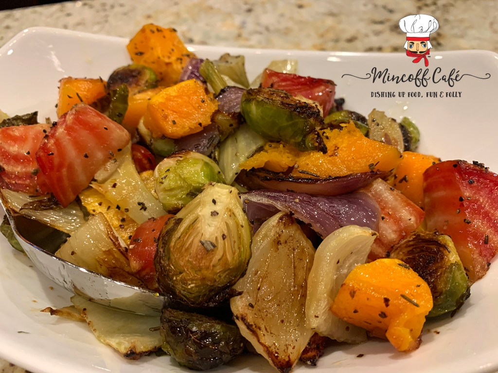 Colorful roasted vegetables ((butternut squash, red onions, brussles sprouts, fennel bulb and candy cane beet root) in a white bowl.