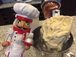 Homemade English muffin dough on beater of a stand copper colored stand mixer with a nutcracker that looks like a chef to the left.