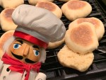 Close up of homemade English muffins. One is split open and there is a nutcracker who looks like a chef in the foreground.