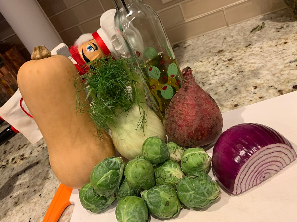 Pepe the nutcracker who looks like a chef hiding behind fall veggies that are going to be roasted. Butternut squash, fennel bulb, red beet, red onion and brussels sprouts