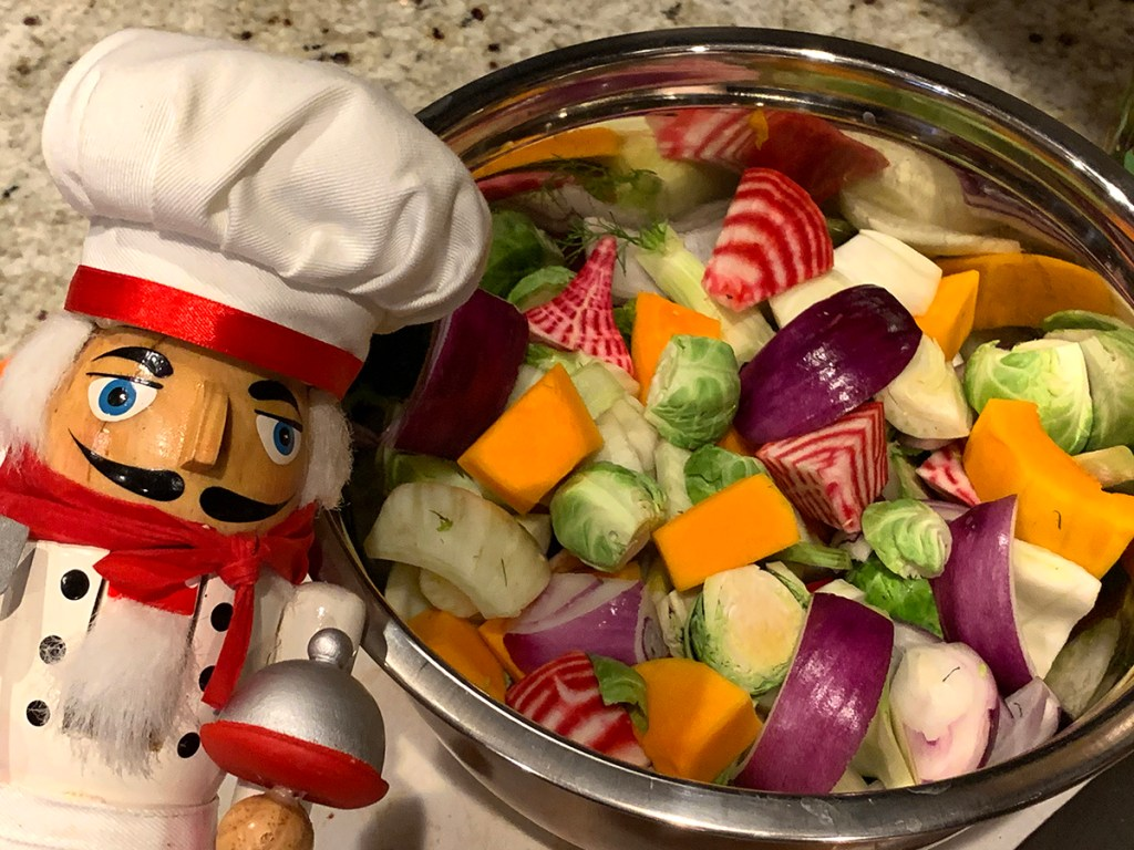 A stainless steel bowl of colorful, mixed, fall vegetables (butternut squash, red onions, brussles sprouts, fennel bulb and candy cane beet root) with a nutcracker who looks like a chef in the left foreground.