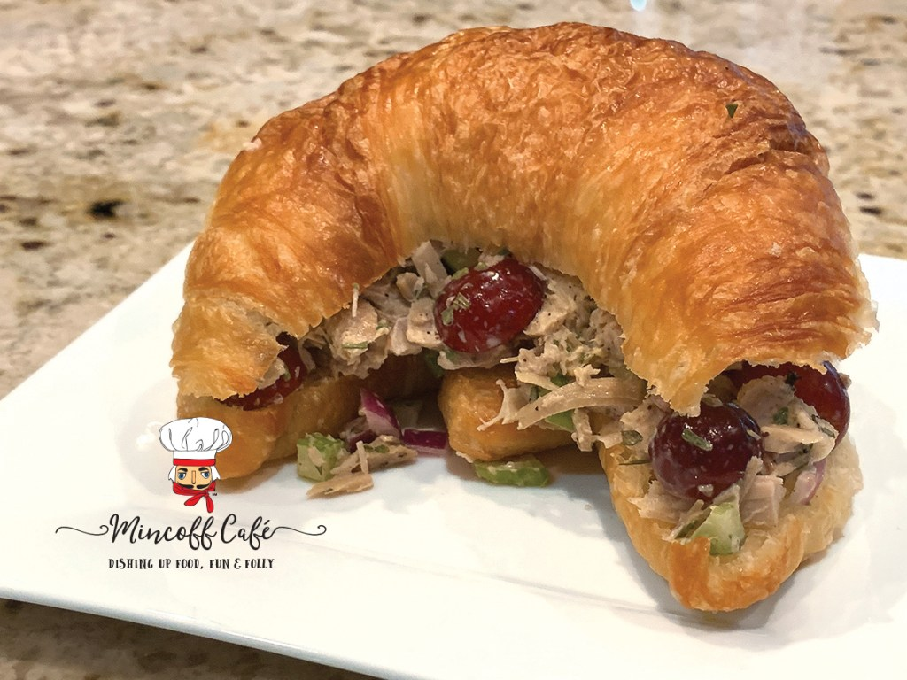Turkey salad sandwich with turkey, celery, red grapes and onions on a croissant, sitting on a white square plate.