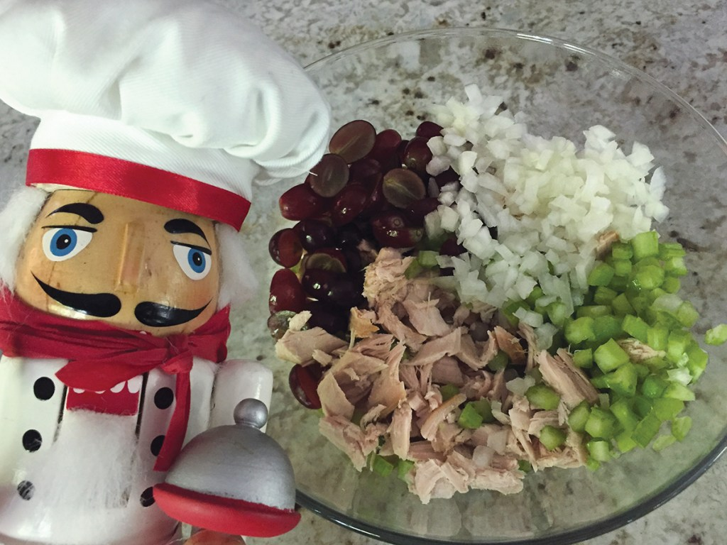 Chopped smoked turkey, celery, onions and red grapes in a clear glass bowl with a nutcracker that looks like a chef in the foreground to the left.