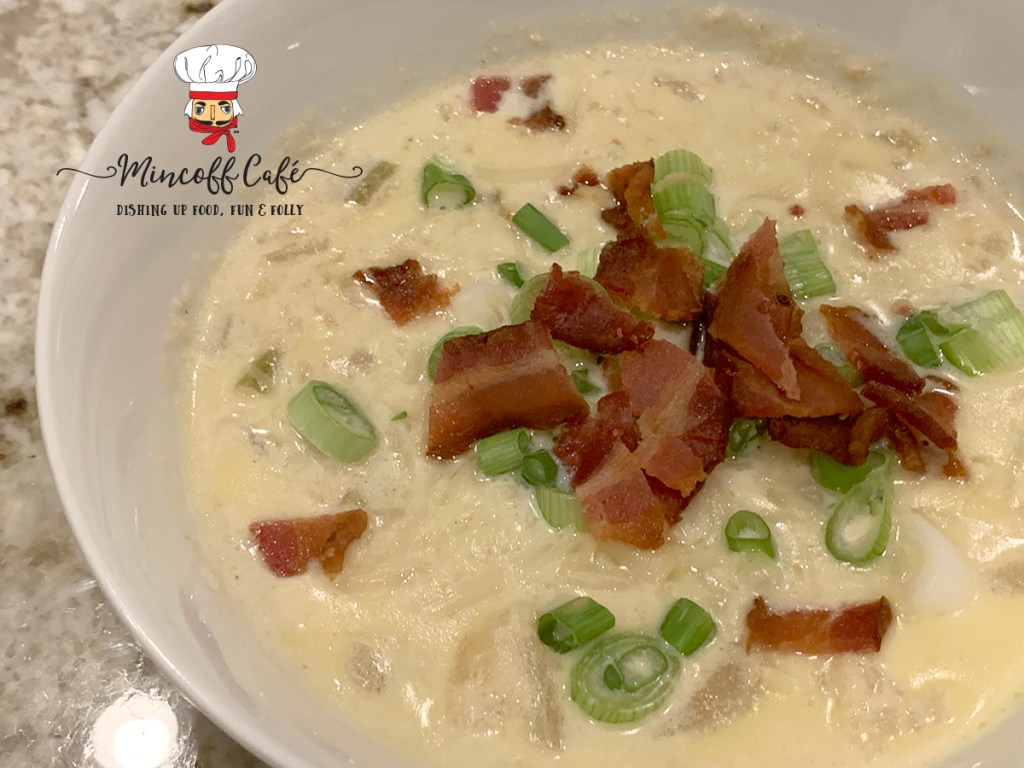 Pale yellow cauliflower soup in a white bowl, garnished with chopped green onions and bacon.