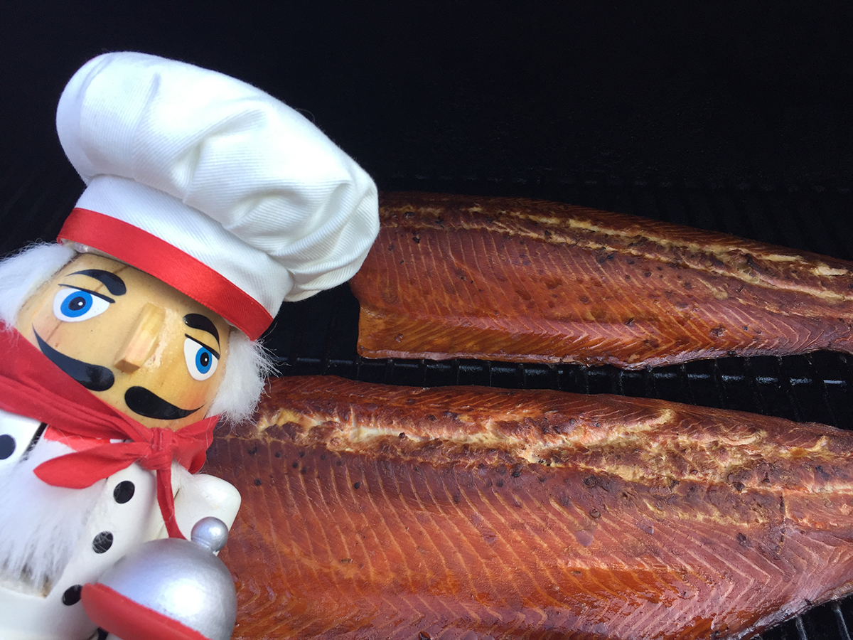 Two smoked wild salmon filets on the grill with a nutcracker who looks like a chef in the foreground on the left.