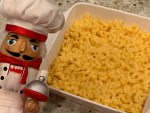 Mac and cheese in a square white casserole dish with a nutcracker in foreground that looks like a chef.