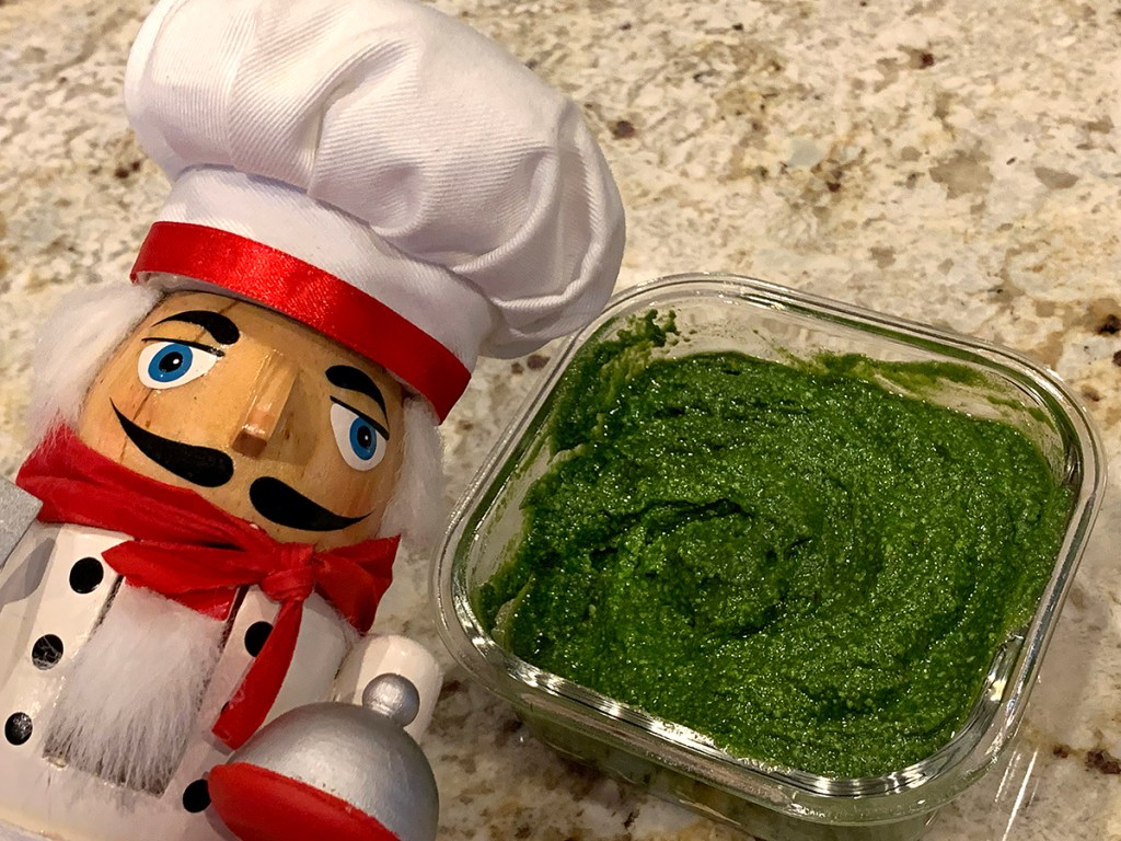 Stinging nettle pesto in a square glass dish. And a nutcracker who looks like a chef in the foreground.