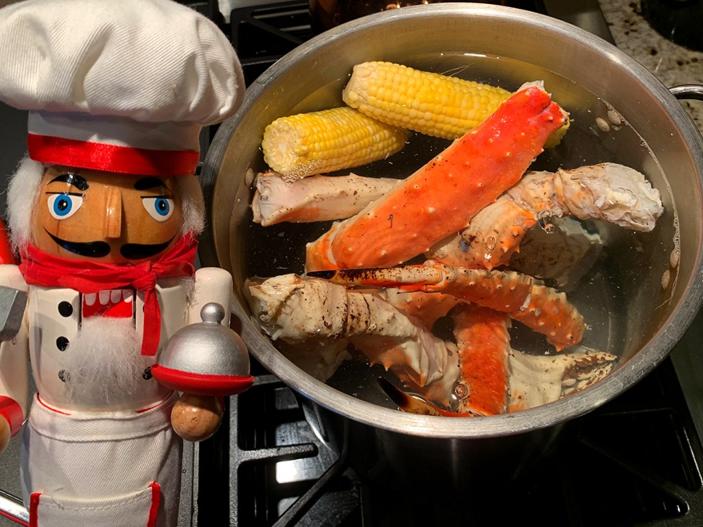 Alaskan King Crab legs and two ears of corn cooking in a large pot. There's a nutcracker who looks like a chef in the foreground.
