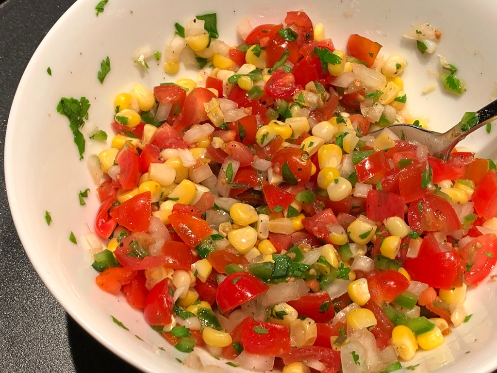 Pico de gallo made of chopped tomatoes, onions, jalepenos, cilantro, yellow corn and lime juice in a round white bowl.