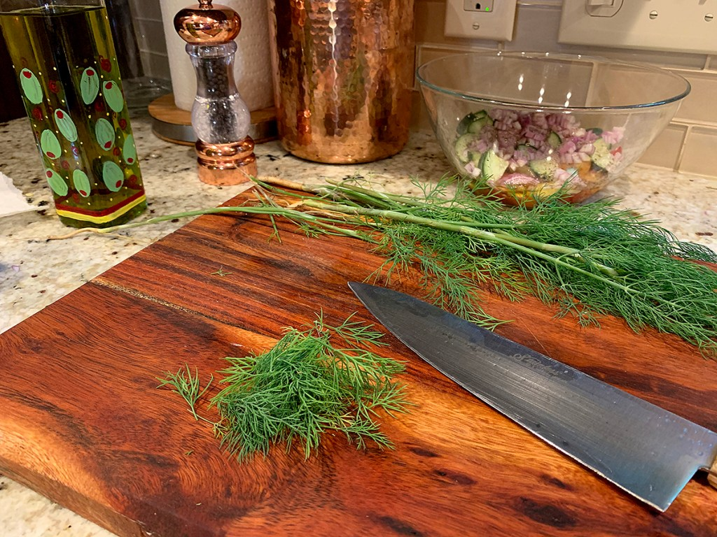 Fresh dill weed sitting on a cutting board waiting to be roughly chopped.