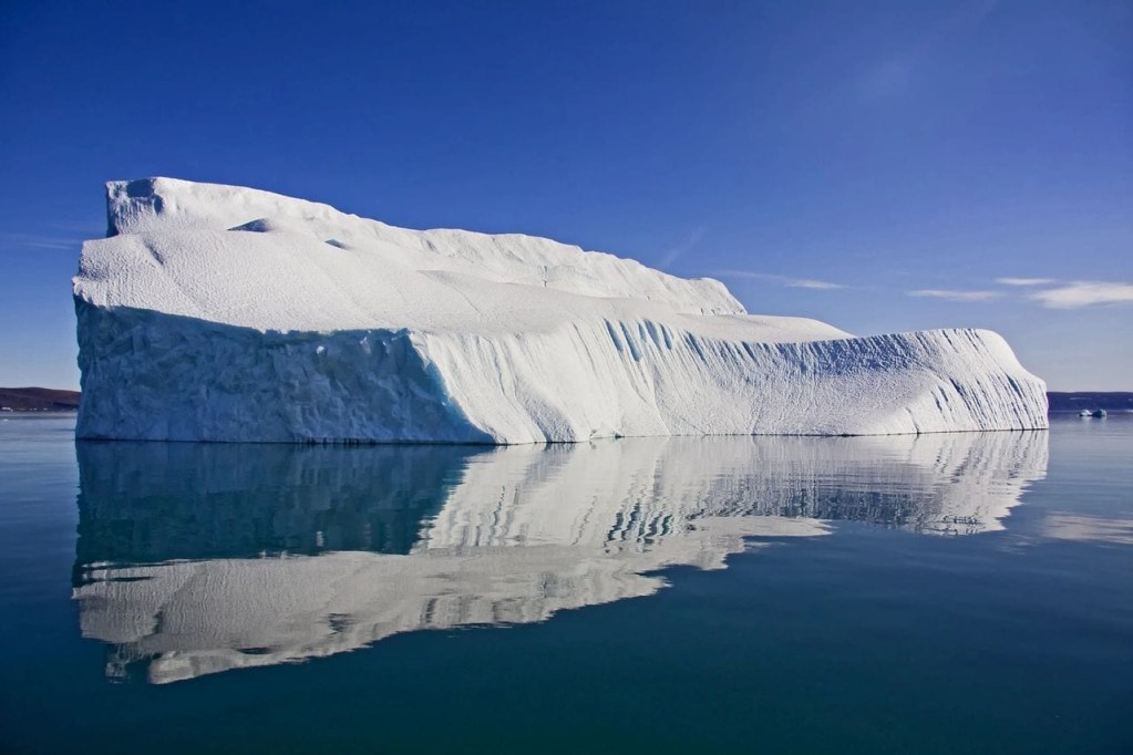 An Iceberg in calm water against blue skies, representing the depth of scars and the implications on the body for NKT