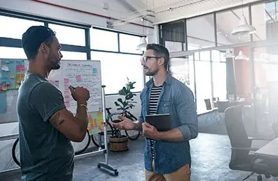 Two business people standing in front of a whiteboard covered in notes inside a modern office discussing digital solutions
