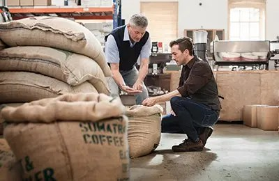 Male owner of a coffee roasting business talking with one of his workers in their warehouse
