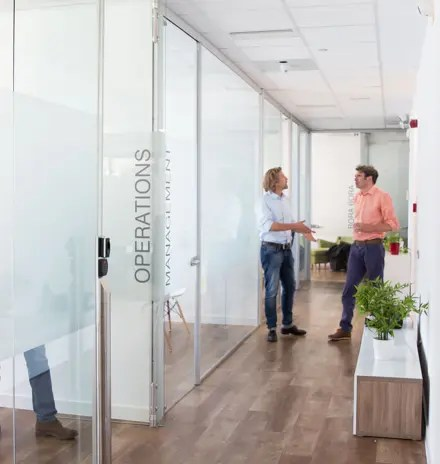 Two male members of Mindcurv team conversing in the hallway of Spanish office in Alcobendas, Madrid.