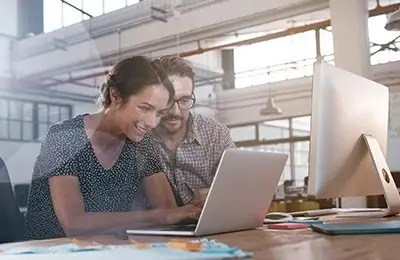 A female and male employees working together on a laptop in a creative digital agency
