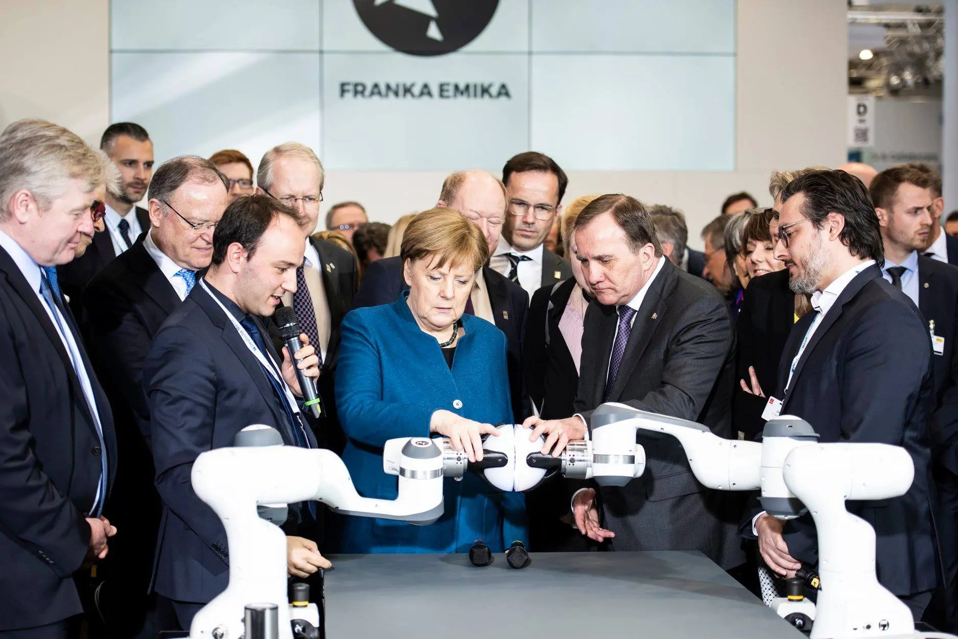 Angela Merkel and Prime Minister of Sweden Stefan Löfven touching the arm of Franka Emika's Panda robot.