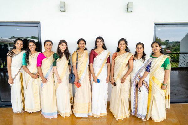 Female Mindcurv members posing in traditional dresses during their Onam celebration