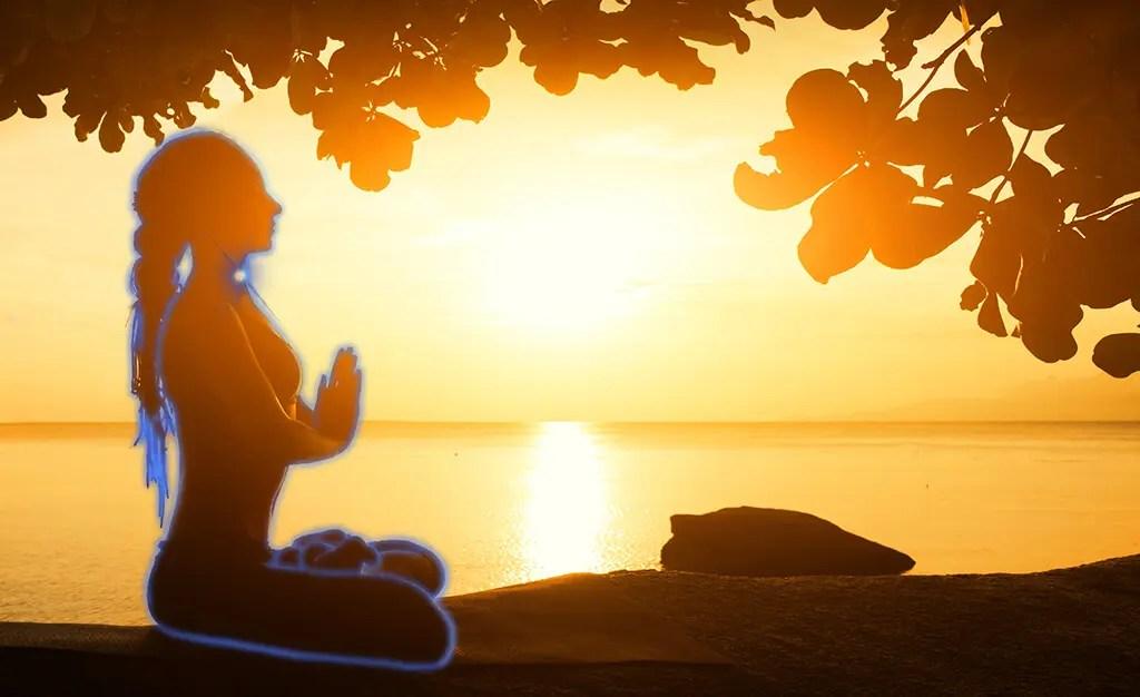 A women meditates to her blue aura