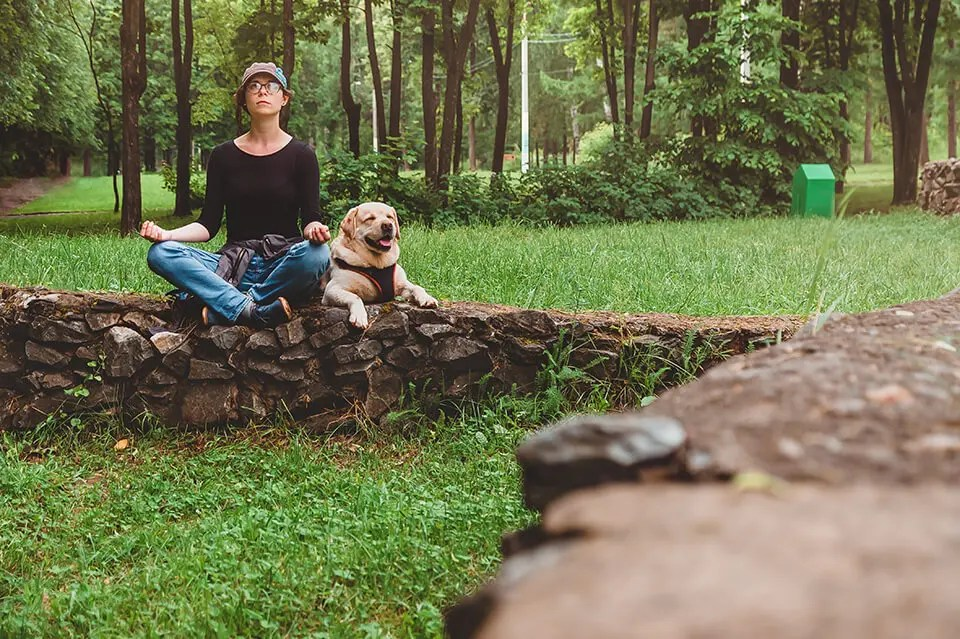 A woman is meditating in nature with her dog.