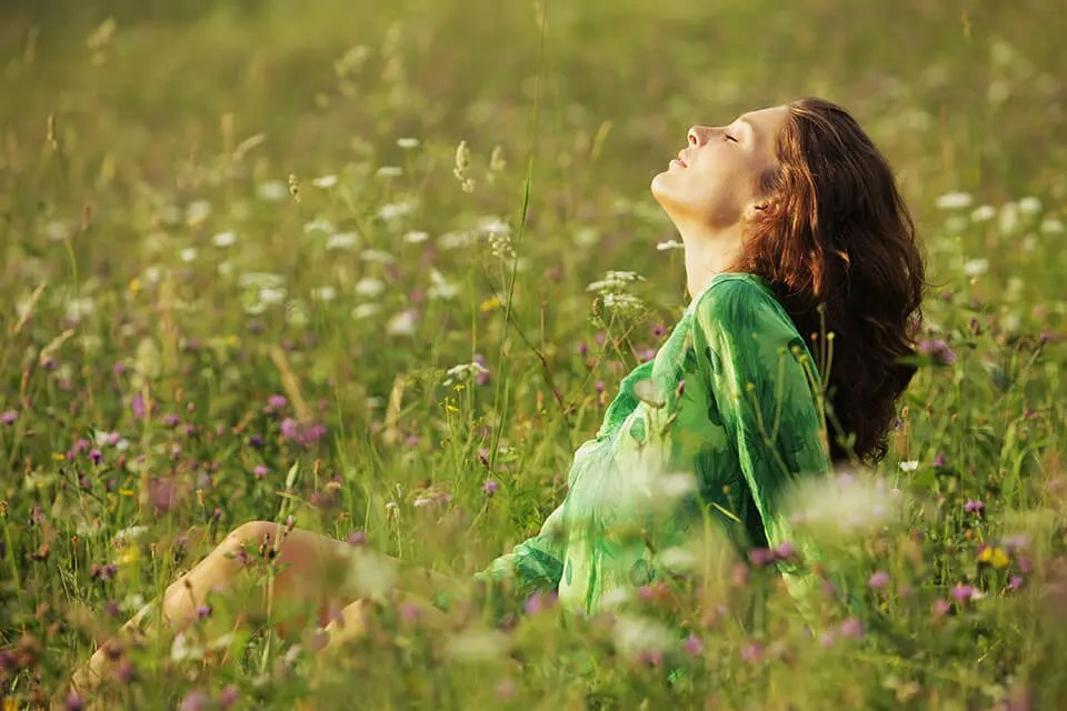 A woman is meditating in nature, observing the sounds around her.
