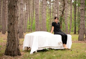 Jennifer sitting on massage table in pine forest