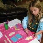A girl painting pastel colors onto birdhouse sections.