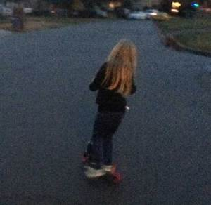Blonde-haired girl riding a pink-wheeled scooter in a the last light of dusk.