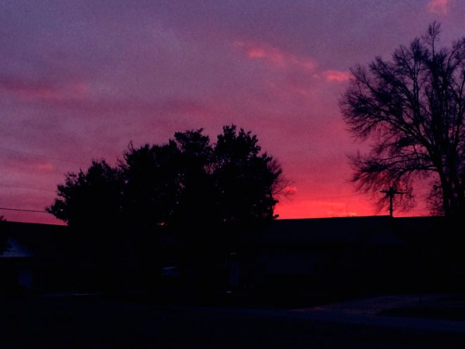A vibrant purple and pink sunset over a shadowed neighborhood.