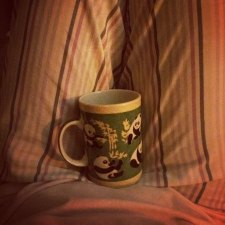 A green tea cup with panda bears perched on a lap with a backdrop of pin-striped pajamas.