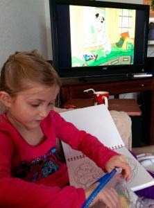 Blonde girl coloring with 101 Dalmations movie playing in the background.