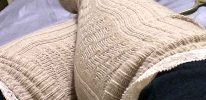 Cream-colored boot socks crossed on blue bed sheets.
