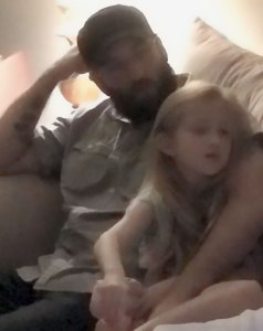 Bearded man in black hat, sitting on couch with his arm around blonde girl, wathching television.