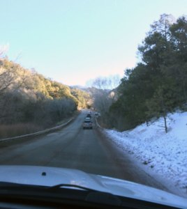 Driving down a steep grade with snow on one side and dry brush on the other.