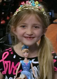 A smiling, blonde girl wearing a costume crown and holding a Cinderella doll.