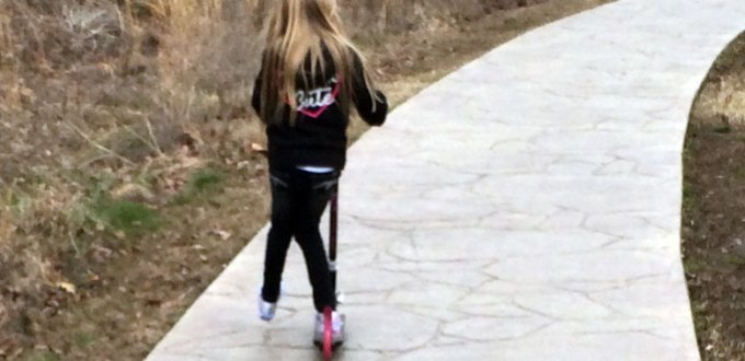 Blonde girl in black sweater and jeans riding her scooter down a winding path.