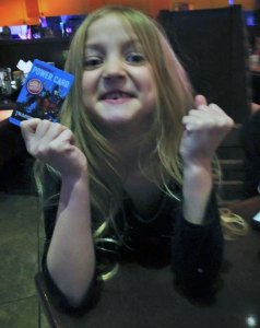 Blonde girl with victorious, clenched-fists holding a rewards card.